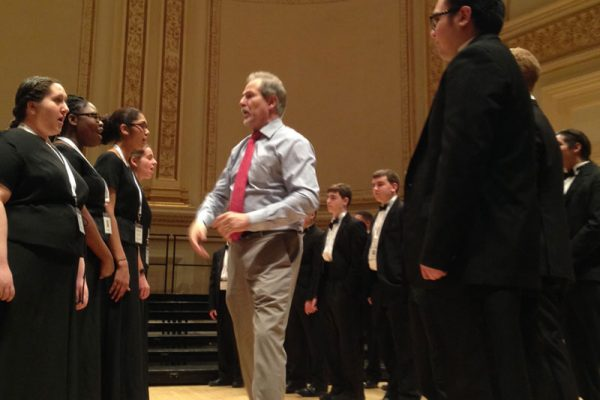 Randall at Carnegie Hall, working with an ensemble on the importance of connecting the body, face and music into the communication of a work.